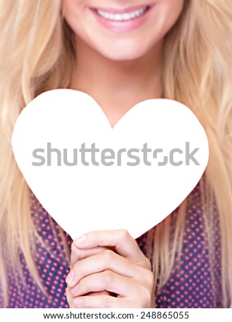 Closeup photo of happy smiling woman holding in hands white paper heart shaped greeting card, healthy lifestyle, romantic Valentine day, love or good health concept - stock photo