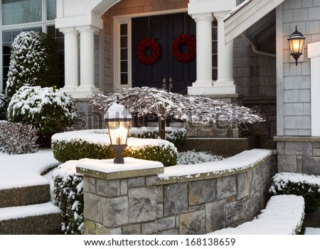 Closeup photo of home entrance during the holidays with fresh snow  - stock photo