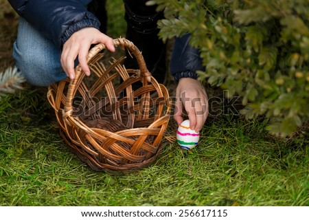 Closeup photo of little girl putting colorful Easter egg in the basket - stock photo