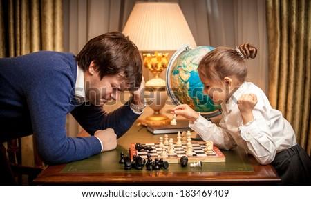 Closeup photo of little girl won chess at man - stock photo