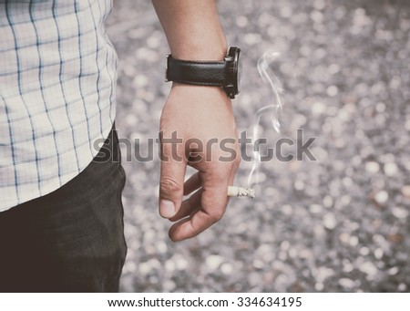 Closeup photo of man hold a Cigarette in outdoor and wearing a black watch: Substance abuse destroys health. - stock photo