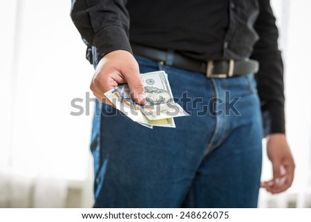 Closeup photo of man in jeans and shirt holding hundred dollar banknotes - stock photo