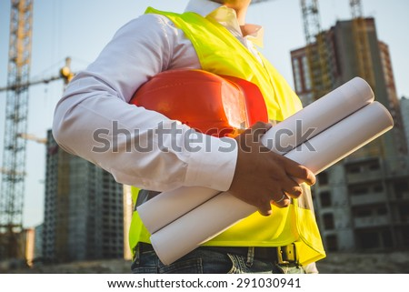 Closeup photo of man in shirt and jacket holding hardhat and blueprints on building site - stock photo