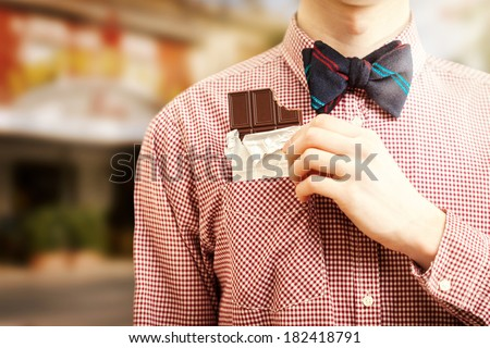 Closeup photo of man taking chocolate out of pocket at street - stock photo