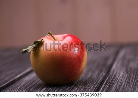 Closeup photo of one whole ripe pure red yellow apple with green leaf on shank on wooden table on beige wall background, horizontal photo