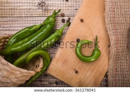 Closeup photo of overturned basket with raw green capsicums with plank burlap and black pepper on brown wooden table, horizontal picture - stock photo