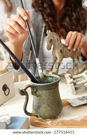 Closeup photo of painting female hand with paintbrush and wooden horse. - stock photo
