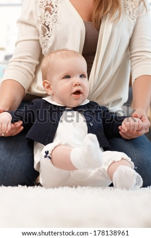 Closeup photo of pretty baby girl sitting on floor, mother holding hands. - stock photo