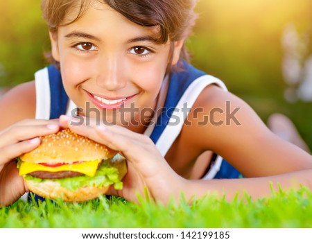 Closeup photo of pretty boy bite tasty big cheeseburger, enjoying picnic outdoors in summer time, unhealthy food