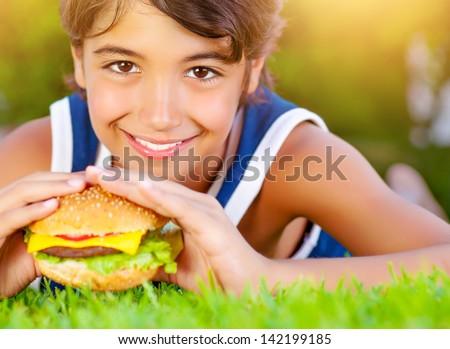 Closeup photo of pretty boy bite tasty big cheeseburger, enjoying picnic outdoors in summer time, unhealthy food - stock photo