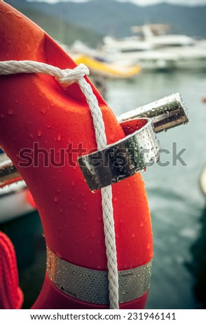 Closeup photo of red lifebuoy with rope against sea port - stock photo