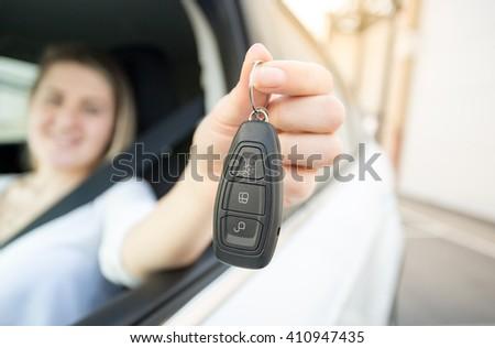 Closeup photo of smiling woman driving a car holding car keys - stock photo