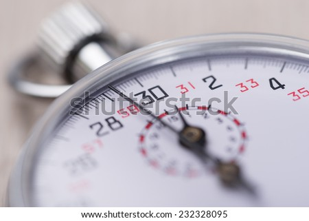 Closeup photo of stopwatch on wooden table - stock photo