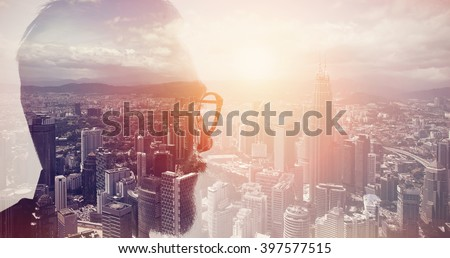 Closeup photo of stylish bearded banker wearing glasses and looking city. Double exposure, panoramic view contemporary megalopolis background. Space for your business message. Wide, sunset effect - stock photo