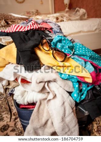 Closeup photo of sunglasses lying on unpacked suitcase - stock photo