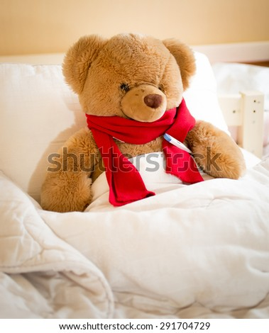 Closeup photo of teddy bear in red scarf lying in bed - stock photo