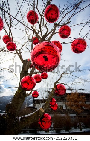 Closeup photo of tree on street decorated with big red balls - stock photo