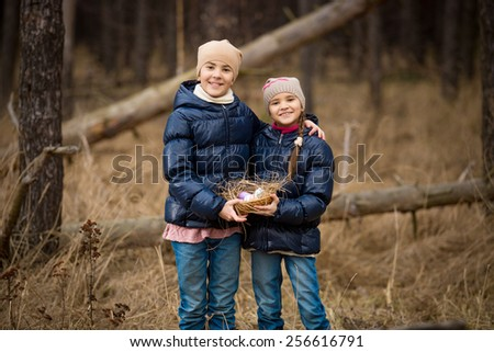 Closeup photo of two happy girls holding basket full of Easter eggs - stock photo
