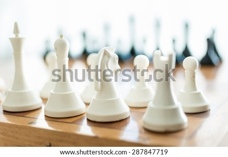 Closeup photo of white chess piece set on wooden board - stock photo