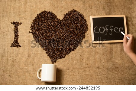 """Closeup photo of woman drawing """"I love coffee"""" on board with chalk and beans - stock photo"""