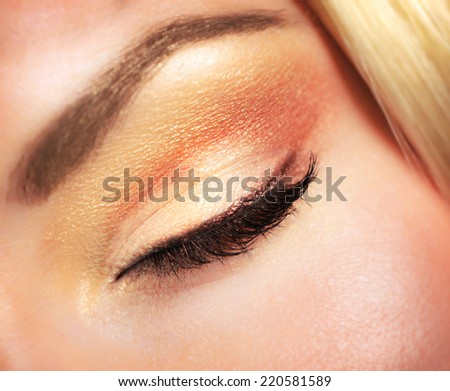 Closeup photo of woman's closed eye with beautiful golden autumnal makeup, face part of attractive model, beauty and style concept