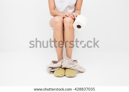 Closeup photo of woman sitting on toilet and using toilet paper. - stock photo