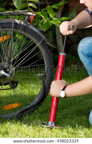 Closeup photo of young man pumping bicycle tyre