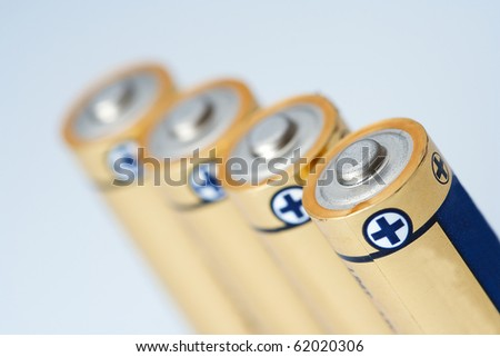 Closeup photo on small battery with positive and negative signs. - stock photo