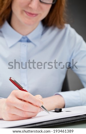 Closeup photograph of a young businesswoman smiling and signing a contract.
