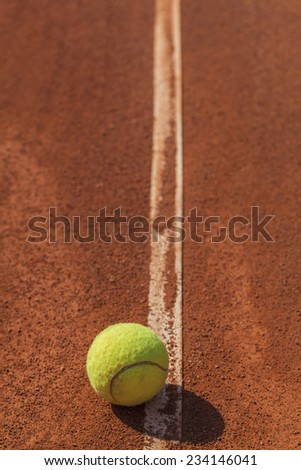 Closeup photograph of tennis ball on the line at clay court - stock photo