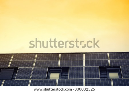 Closeup photovoltaic solar panels on house roof with open windows and  with shut blinds against sunny yellow sky renewable power energy, horizontal picture  - stock photo