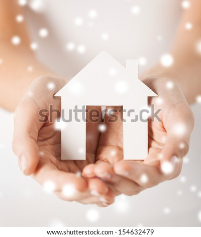 closeup pi??ture of woman hands holding paper house - stock photo