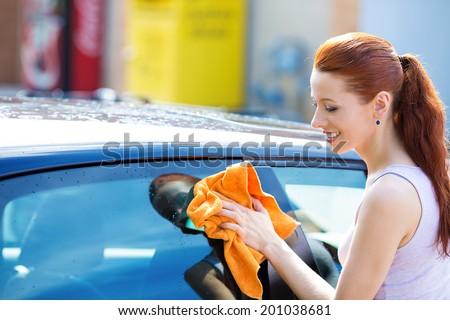 Closeup picture, image young woman, driver, dry wiping  her car with microfiber cloth after washing it, cleaning auto, automobile windows. Transportation self service, care concept. Paint protection - stock photo