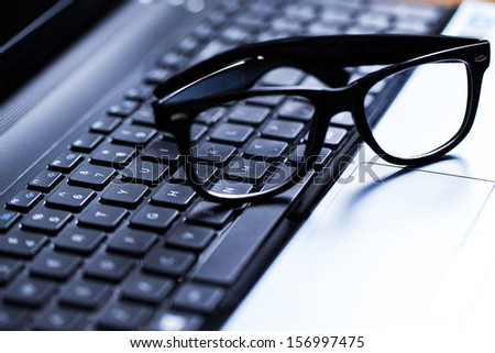 Closeup picture of a glossy laptop keyboard with glasses above it