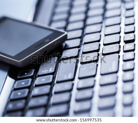 Closeup picture of a keyboard with a phone lying above it - stock photo