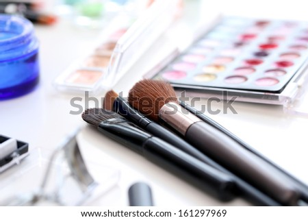 Closeup picture of a large variety of colorful cosmetic poweder and a cosmetic brush - stock photo