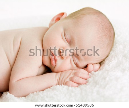 closeup picture of a newborn baby's face while it is sleeping - stock photo