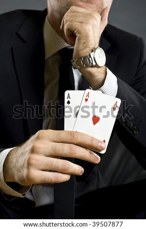 closeup picture of a pair of aces held by a businessman
