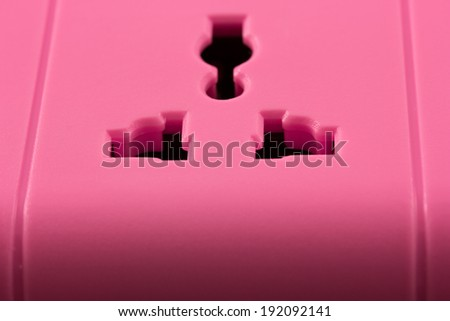 Closeup picture of a pink outlet isolated on black. Electric Power Line on balck background - stock photo