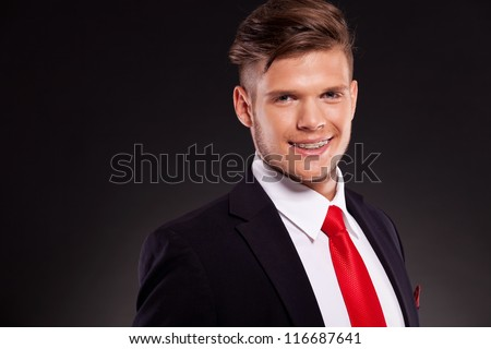 closeup picture of a young business man looking into the camera with a big smile on his face, revealing braces. on dark background - stock photo