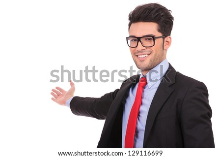 closeup picture of an attractive young business man presenting something in the back while looking at the camera and smiling, on a white background - stock photo