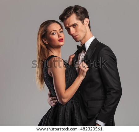 closeup picture of an elegant couple standing embraced on grey background