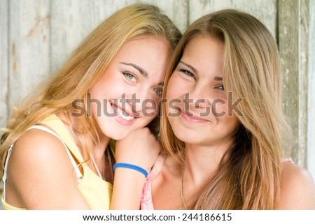 closeup picture of 2 beautiful young ladies hugging together - stock photo