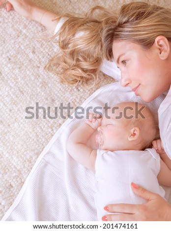 Closeup picture of beautiful young mother lying down with her sweet sleeping newborn child, loving family, new life concept - stock photo