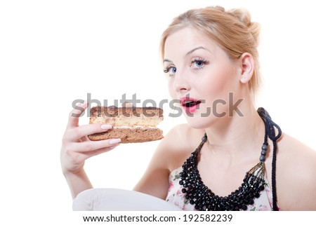 closeup picture of blue eyes beautiful blond young woman having fun eating along large chocolate cake happy smiling & looking at camera on white background portrait - stock photo