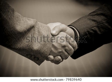 Closeup picture of businesspeople shaking hands, making an agreement. Against pavement. B&W. - stock photo