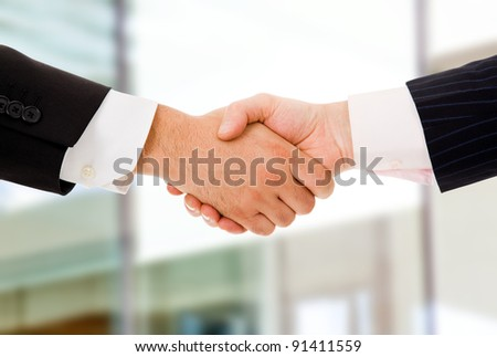 Closeup picture of businesspeople shaking hands, making an agreement at the office. - stock photo