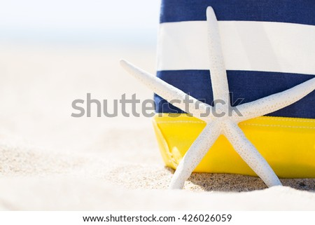 closeup picture of colorful beach bag and starfish at the beach, vacation concept - stock photo