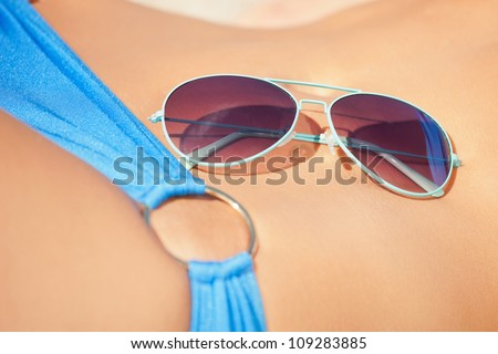 closeup picture of female belly, bikini and shades. - stock photo