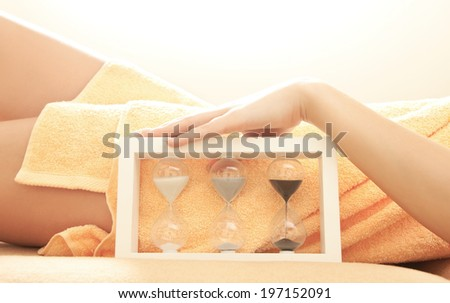 closeup picture of female hands and legs in spa salon with a sandglass - stock photo